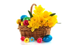 Spring basket with chocolate eggs and flowers.